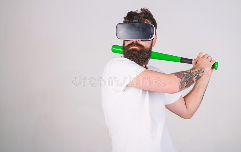 Sportsman with trendy beard mastering his batting skills using digital technology. Bearded man paying baseball in. Virtual reality game. Man in VR glasses with stock photos