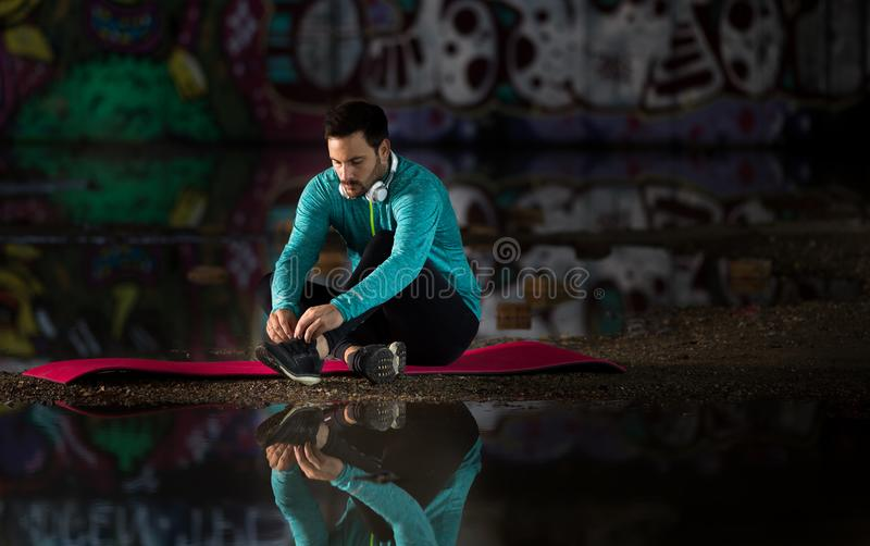 Sportsman tying laces in front of graffiti wall and water stock image