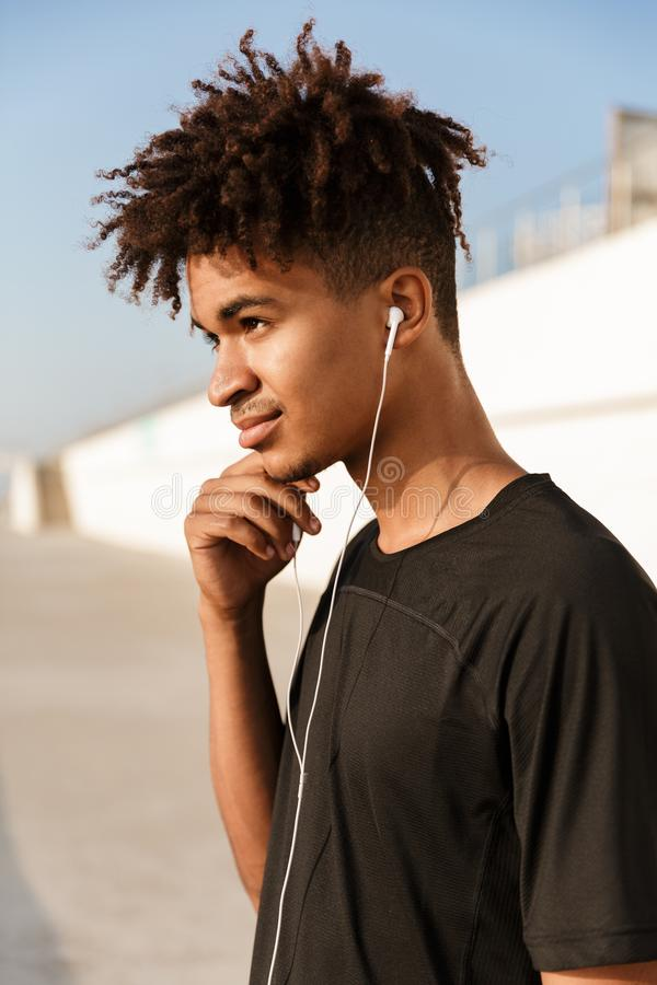 Sportsman walking outdoors on the beach listening music with earphones. Image of a young guy sportsman walking outdoors on the beach listening music with royalty free stock images