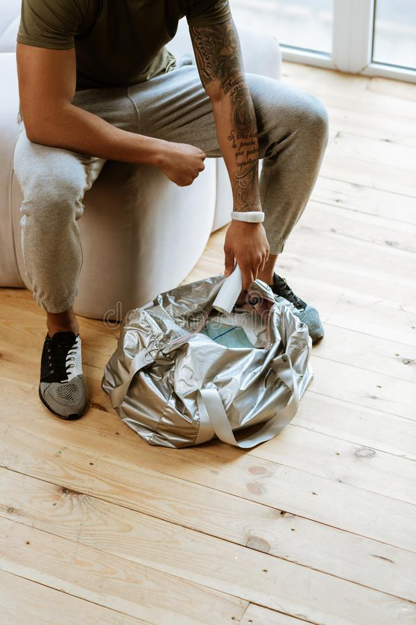 Sportsman wearing grey sport trousers packing his bag for gym. Grey sport trousers. Professional sportsman wearing grey sport trousers sitting and packing his royalty free stock image