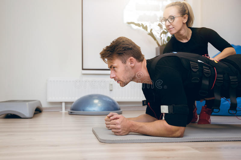 Sportsman working out on the floor with personal coach royalty free stock photos