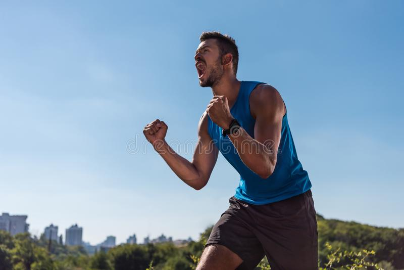 Sportsman yelling and celebrating triumph. Excited sportsman celebrating triumph and yelling, with blue sky on foreground stock images