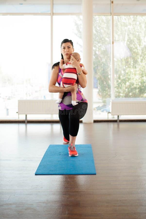 Sportsmate maakt uitvalt vooruit met haar baby stock afbeeldingen