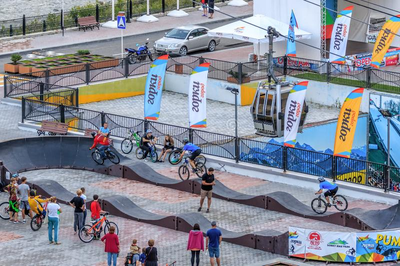 Sportsmen bikers ride bicycles at trial competition on outdoor pump track in Gorky Gorod mountain resort. Bike riders run pursuit royalty free stock photo