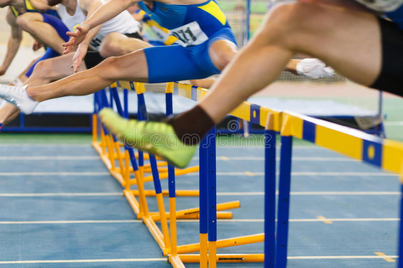 Sportsmen running hurdles sprint race. In indoor track and field competition royalty free stock image