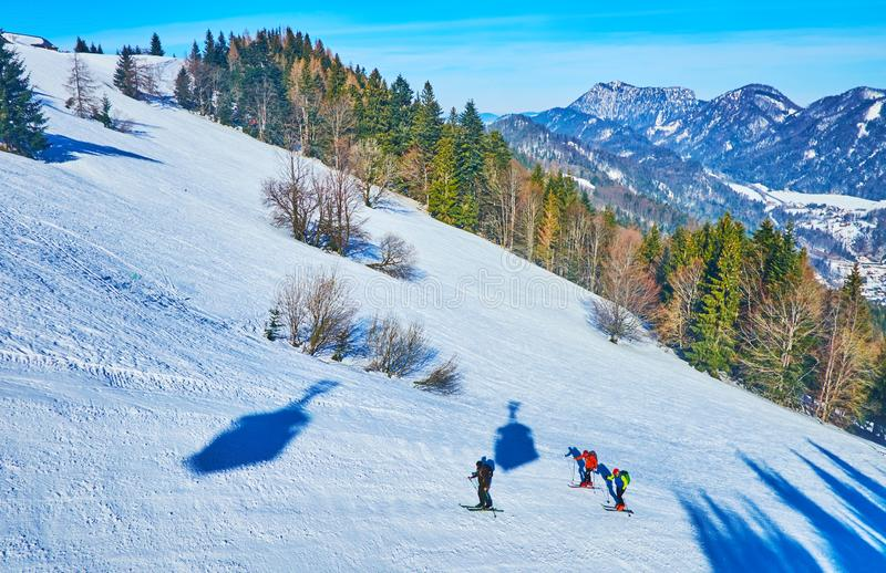 The sportsmen on slopes of Zwolferhorn, St Gilden, Salzkammergut, Austria. Aerial view from the cable car cabin on the slope of Zwolferhorn mount with skiers stock photos