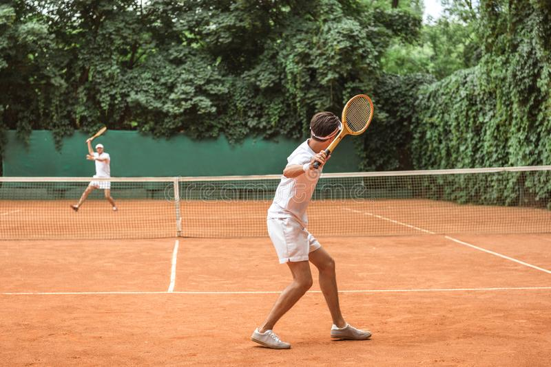 sportsmen in white sportswear playing tennis with wooden rackets royalty free stock photos