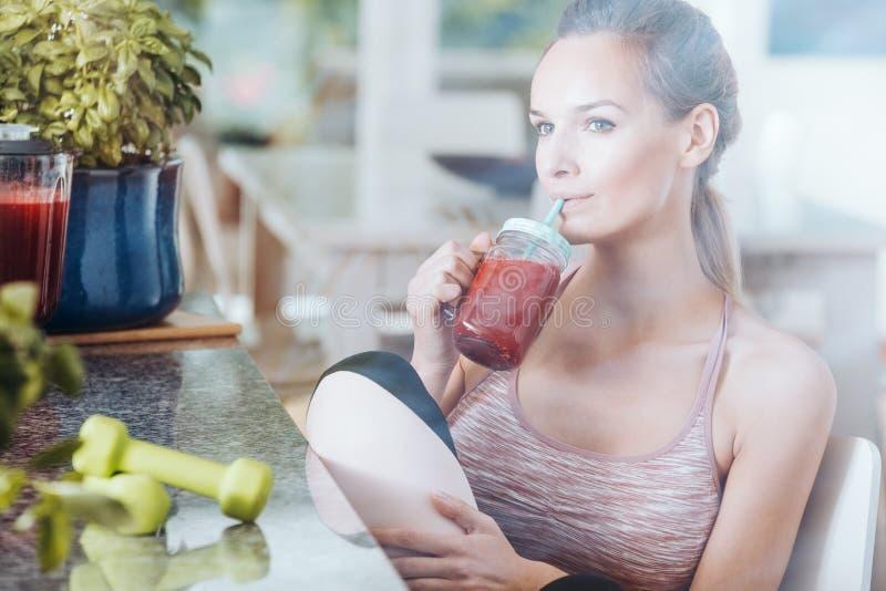Sportsmenka pije zdrowego czerwonego koktajl fotografia royalty free