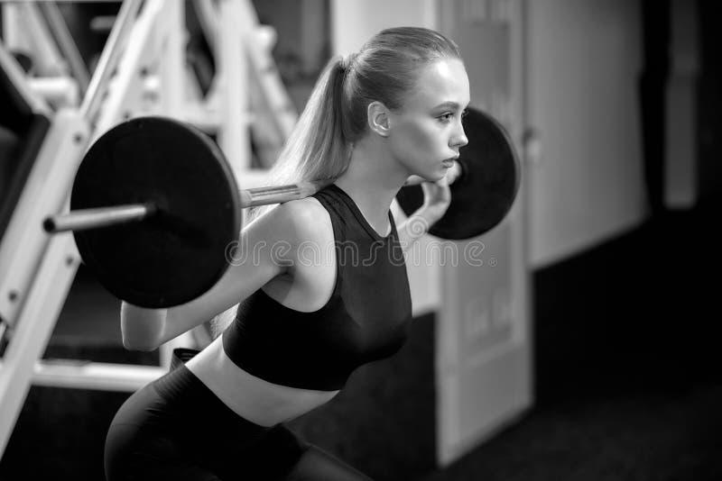 Sportsmenka robi kucnięciom z barberll w gym obrazy royalty free