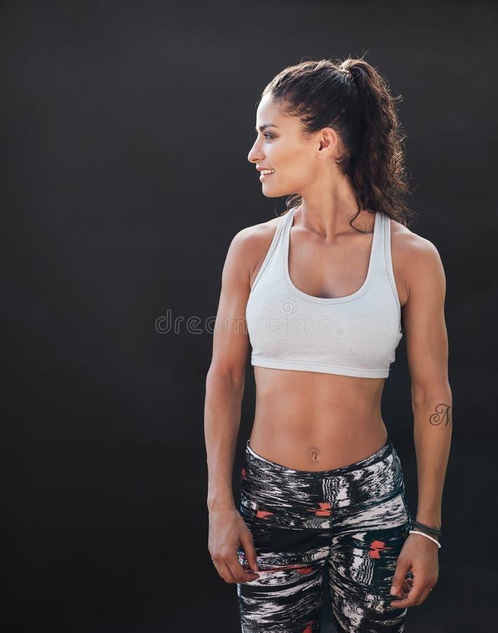 Sportsmenka z mięśniowym ciałem na czarnym tle zdjęcia stock