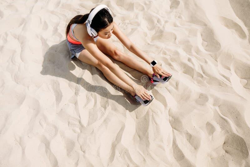 Sportsmenki rozciąganie na piasku obrazy stock