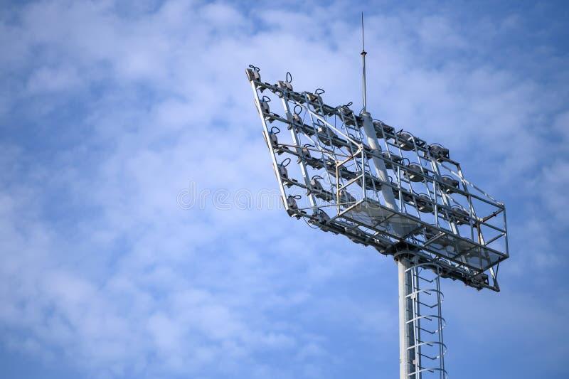 Sportstadionstrålkastare med bakgrund för blå himmel Fotboll- och fotbollljuslampa royaltyfri bild