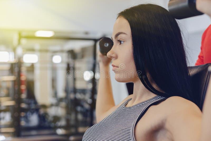 Sportswear маленькой девочки нося в спортзале выполняет тренировки гантели, тренер помогает ей стоковые изображения