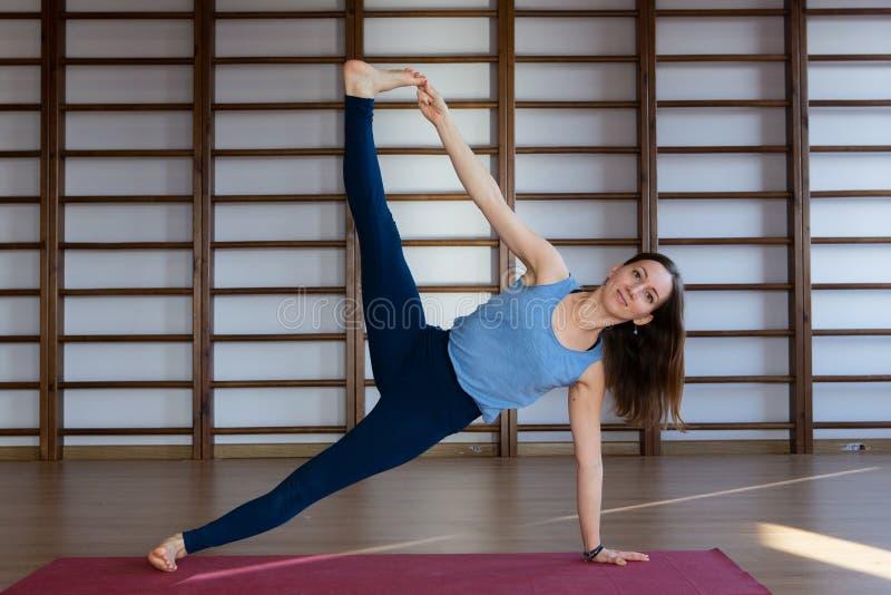 Sportswear branco vestindo da mulher bonita calma nova que dá certo, fazendo o exercício da ioga ou dos pilates Comprimento compl fotos de stock