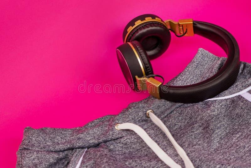 Sportswear et casque sur fond rose Faire du sport Raccourcis et joueur Gros casques sans fil de style noir images stock
