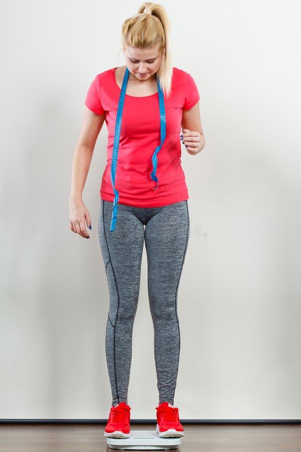 Sportswear vestindo da mulher que está na máquina do peso imagem de stock