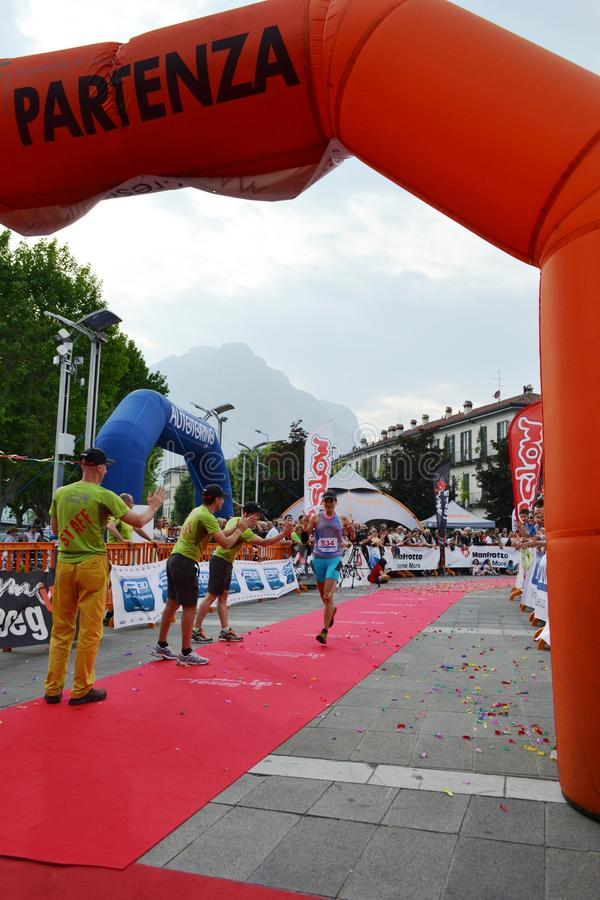 Sportswoman arriving at the finish of `Lecco city - Resegone mountain` running marathon event. stock photo