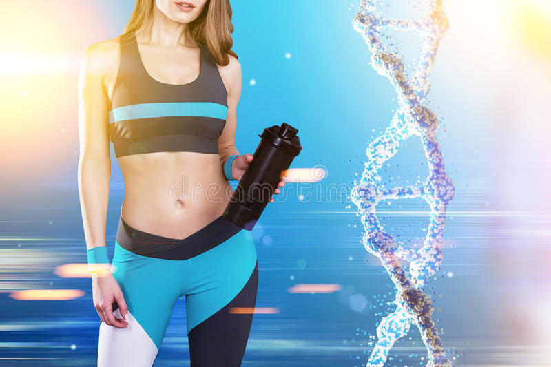 Sportswoman and dna. Close up of a sportswoman wearing a blue, black and white sportswear and standing against blue background with a dna to her right. Toned stock images