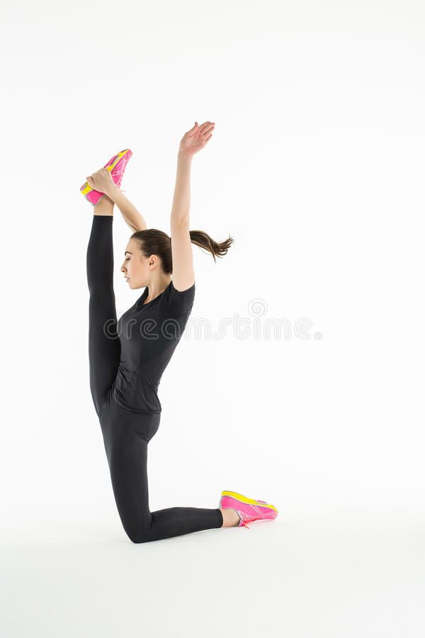 Sportswoman doing difficult exercise for. Stretching. Kneeling raises his hand holding his right leg. Girl dressed in a black T-shirt and shorts. Studio shoot stock image