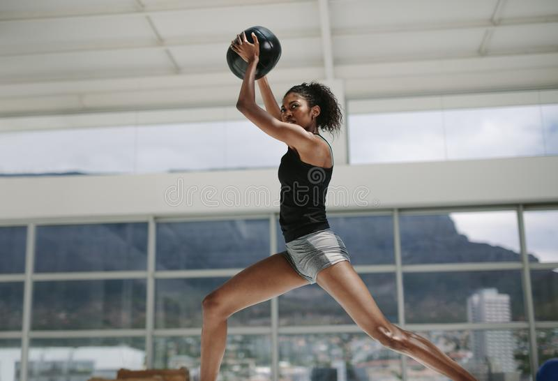Sportswoman doing exercise with fitness ball. Female exercising and stretching with medicine ball at fitness studio royalty free stock photos