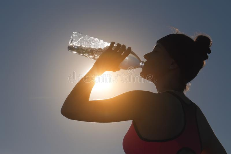 Sportswoman drinking water after training from bottle royalty free stock photo
