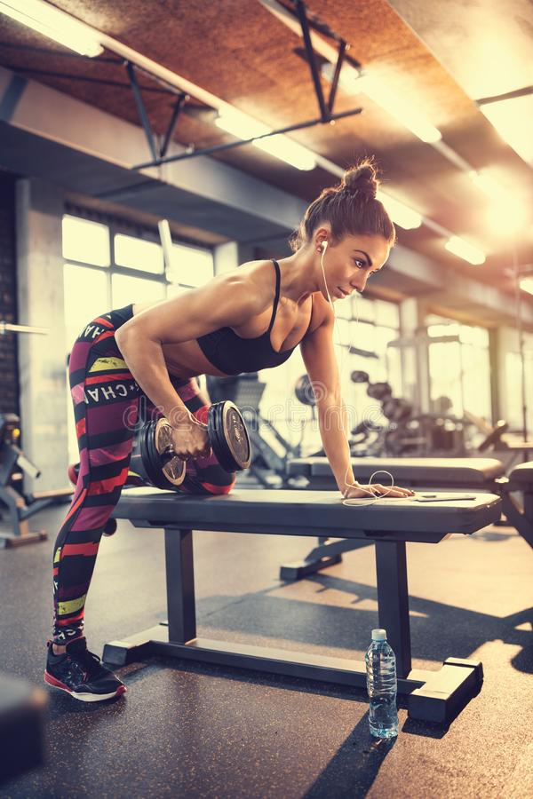 Sportswoman in gym exercise muscles and listen music stock photos