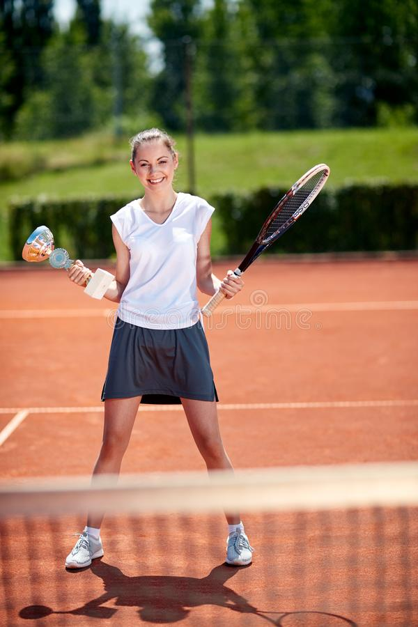 Sportswoman with her goblet and racket. Successful sportswoman with her goblet and racket at tennis court stock image