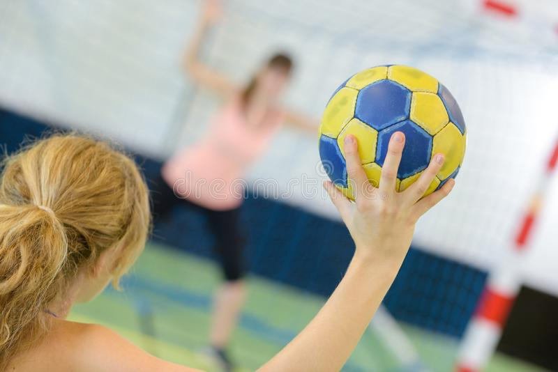 Sportswoman holding ball against handball field indoor royalty free stock images