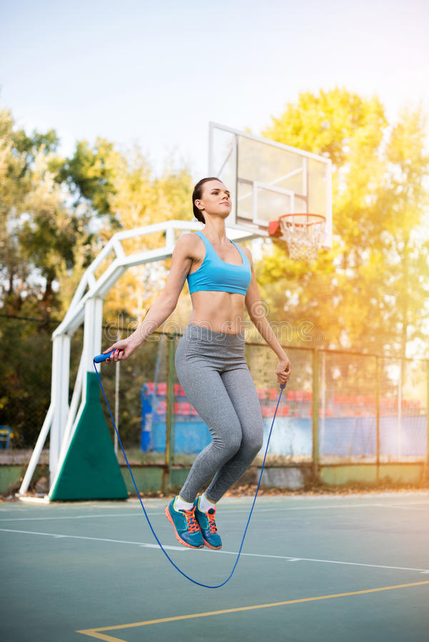 Sportswoman jumping with skipping rope on stadium stock photos