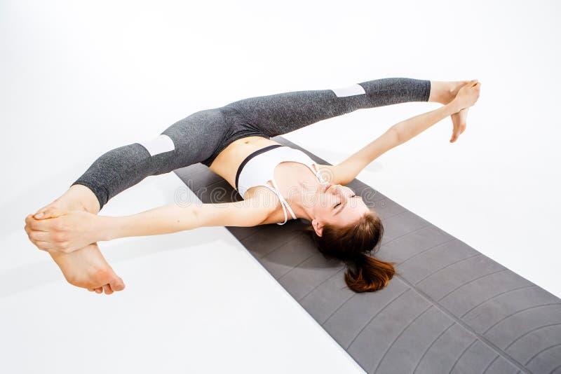 Sportswoman makes twine on rug royalty free stock photos