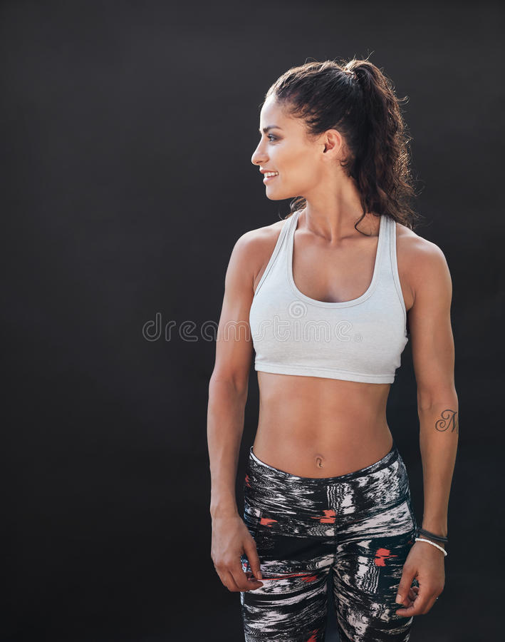 Sportswoman with muscular body on black background. Portrait of young woman with muscular body standing against black background and looking away at copy space stock photos