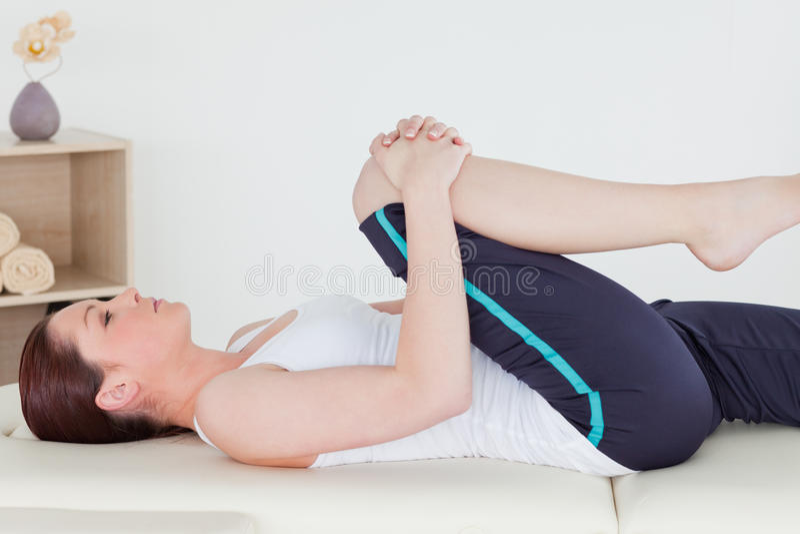 Sportswoman que estica seu pé foto de stock royalty free