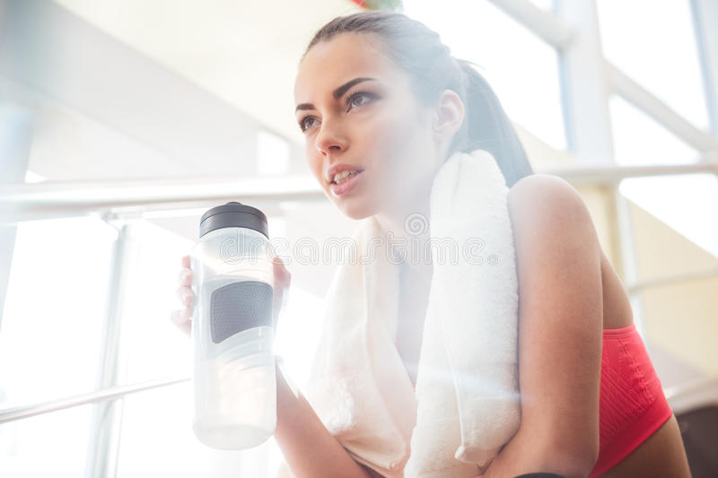 Sportswoman relaxing after training and drinking water in gym royalty free stock photos