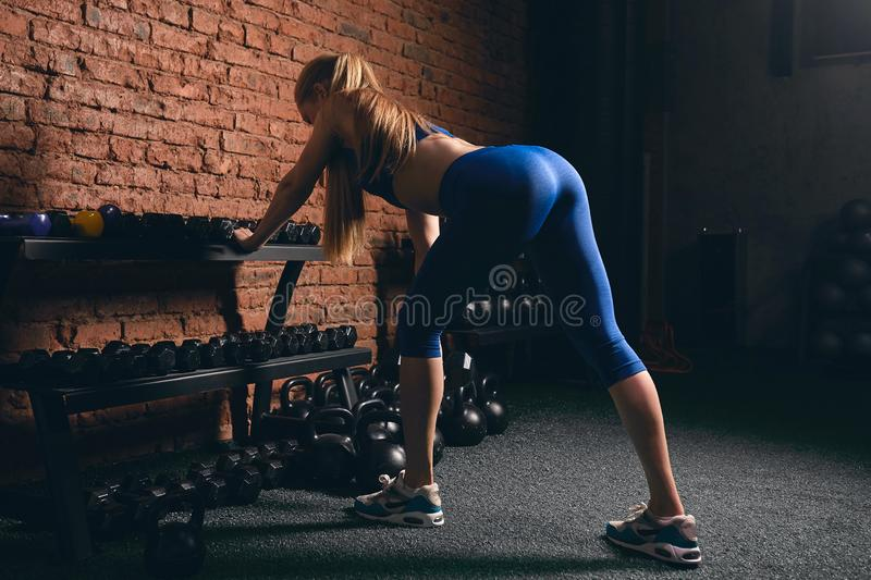 Sportswoman with sexy butt leaning on the shelf. Developing muscles. side view photo.healthy lifestyle royalty free stock photo