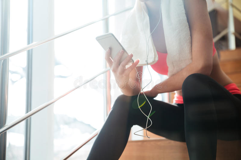 Sportswoman sitting and using smartphone with earphones in gym stock images