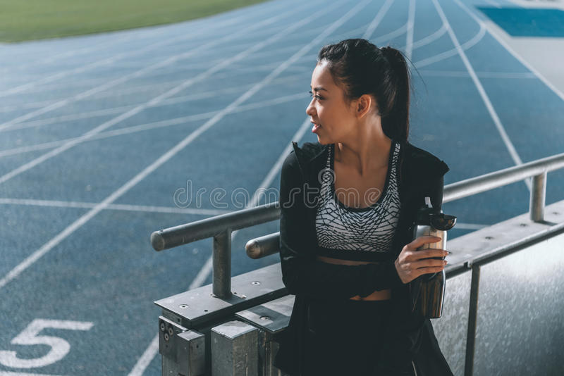Sportswoman with sport bottle on running track on stadium. Asian sportswoman with sport bottle on running track on stadium royalty free stock photo