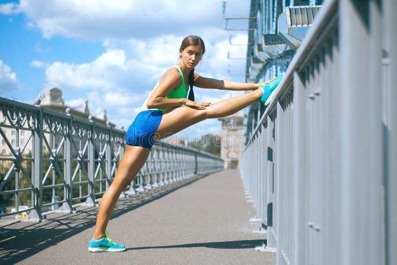 Sportswoman stretching her legs on the metal railing of the brid. Hispanic sportswoman doing stretching exercsice on the bridge royalty free stock image