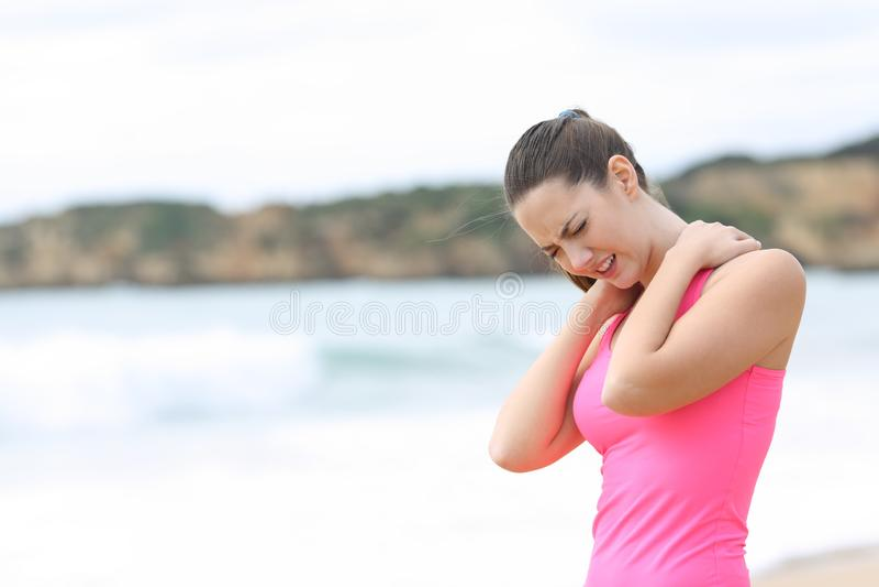 Sportswoman suffering neck ache on the beach royalty free stock photo