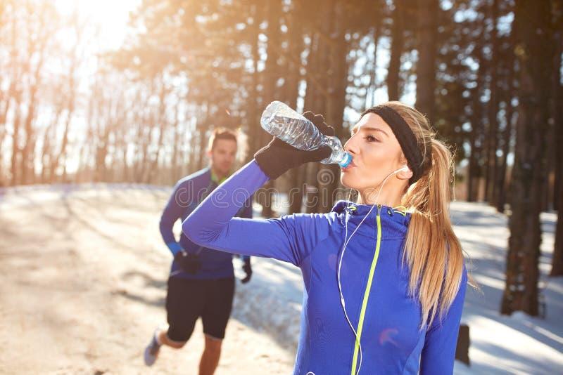 Sportswoman on training drinking water royalty free stock image