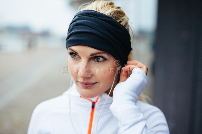 Sportswoman wearing headband and listening to music on earphones. Close-up portrait of beautiful sportswoman wearing headband and listening to music on earphones royalty free stock photo