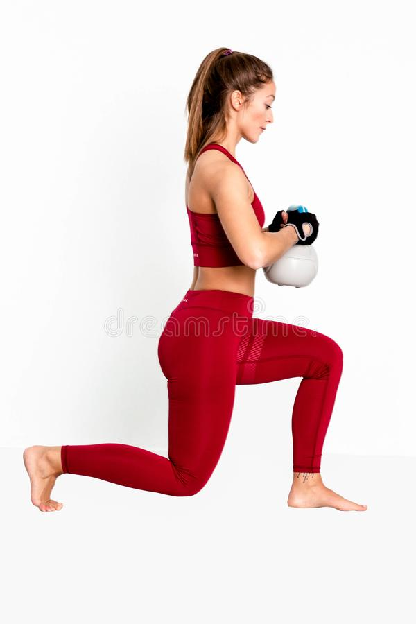 Attractive fit female doing lunge fitness exercise with grey blue kettlebell weight- Image royalty free stock image
