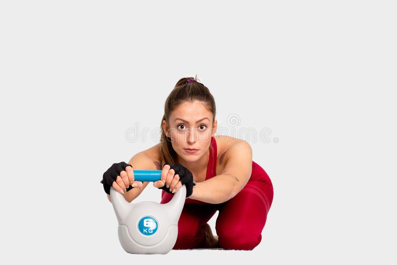Cute girl  in sportswear doing crossfit workout with kettle bell on white background Confident looking forw- Image stock photo