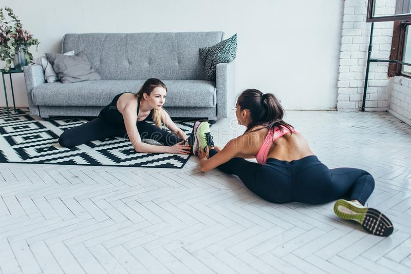 Sportswomen warming-up muscles before workout doing stretching exercise sitting on floor at home.  stock photography