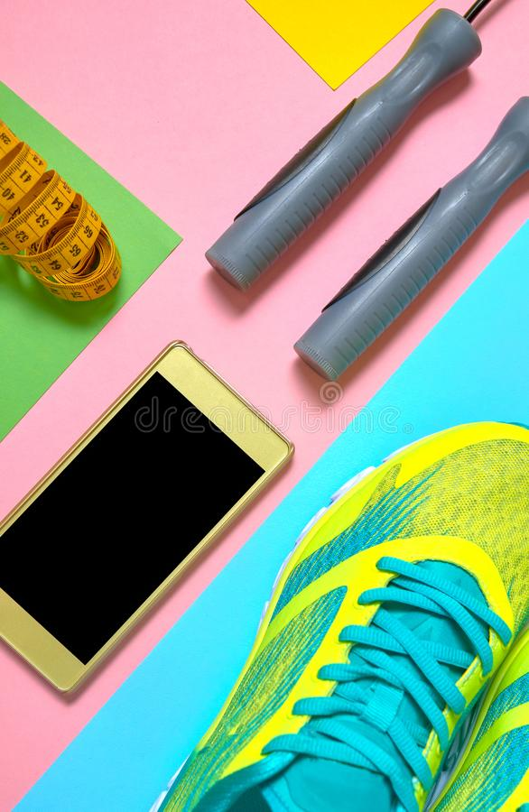 Sportuitrusting met loopschoenen, touwtjespringen, mobiele telefoon met het zwarte scherm en het meten van band op kleurrijke ach stock foto