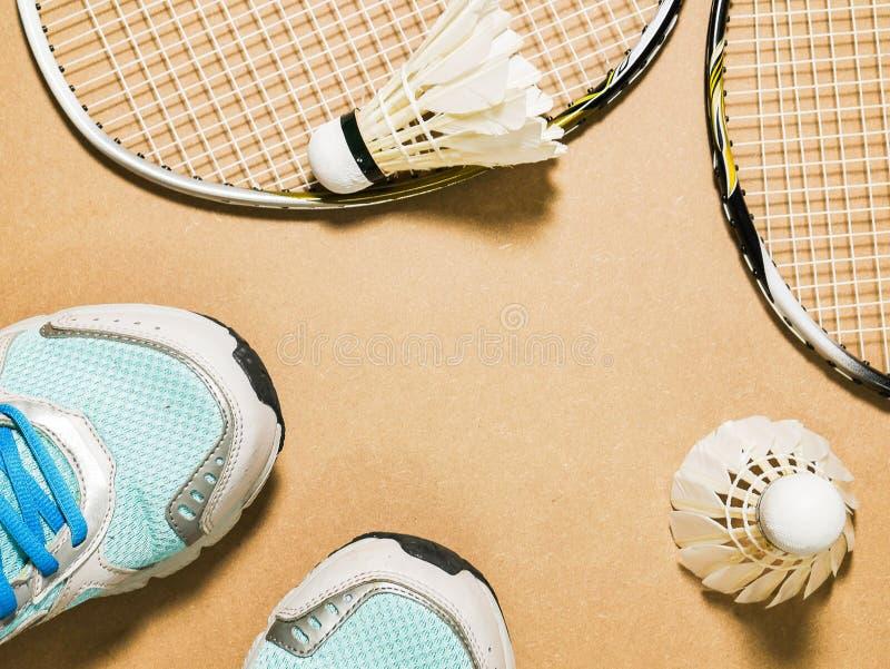 Sportuppsättning av blåa sportskor och fjäderbollar med racket för badminton två på kryssfanerbakgrund arkivbilder
