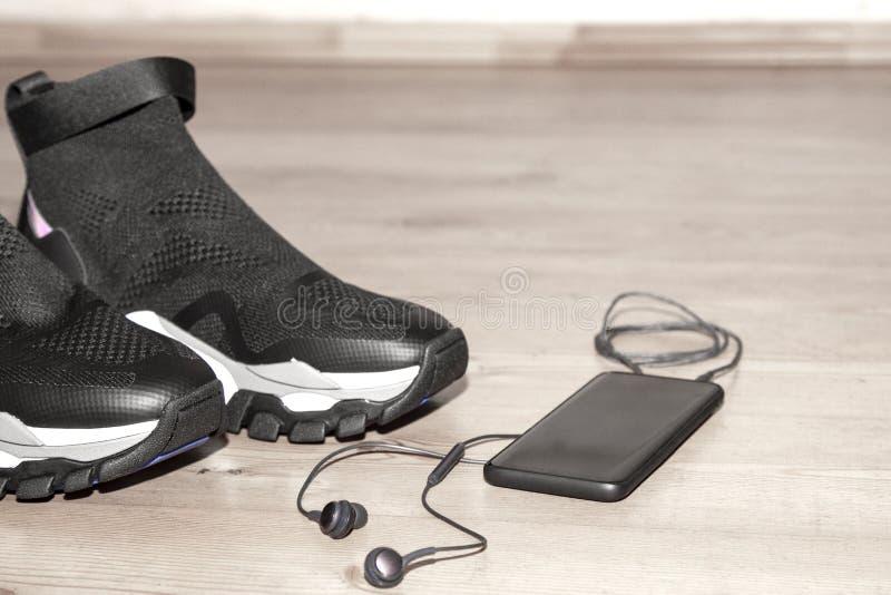 Sportuppsättning, konditiontillbehör på grå bakgrund Modeskodon, hörlurar, telefon för kroppgenomkörare Aktivt livbegrepp royaltyfri fotografi