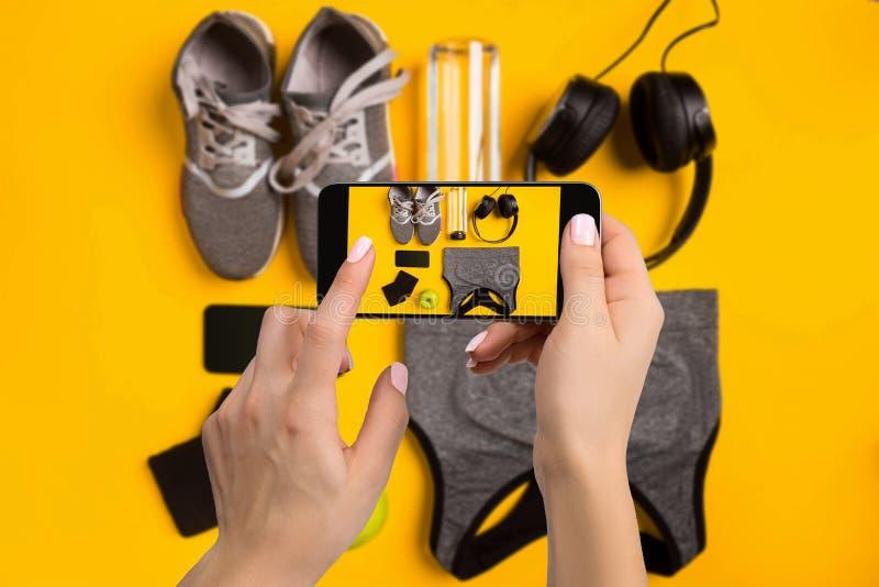 Sportutrustning som fotograferar på mobiltelefonen Smartphone skärm med konditionhjälpmedelbild royaltyfri foto