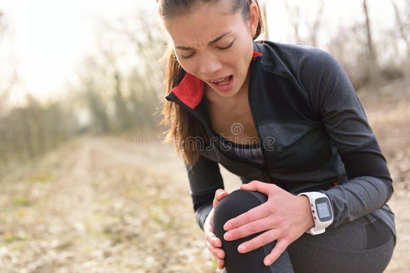 Sportverletzung - Laufsitzfrau mit den Knieschmerz stockfotografie