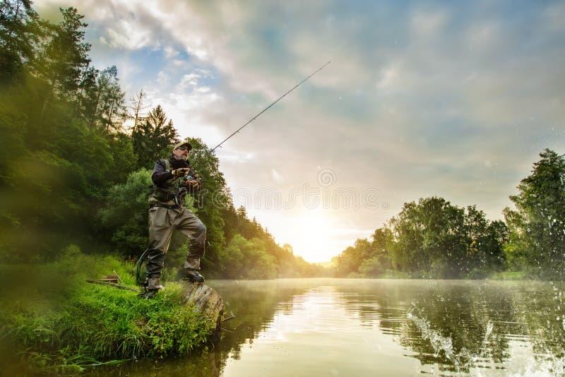 Sportvisser de jachtvissen Openlucht visserij in rivier stock fotografie