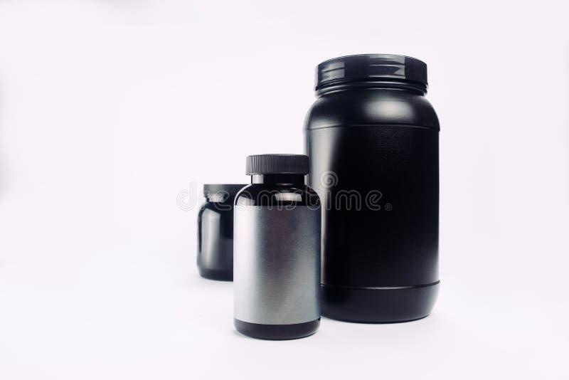 Sportvoeding, Weiproteïne en Gainer Zwarte Plastic Kruiken ISO royalty-vrije stock foto's